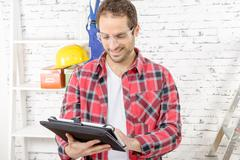 Attractive young man using the tablet for DIY Stock Photos