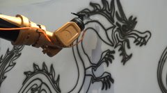 Robot arm paints classic Chinese dragon creating interesting contrast Stock Footage