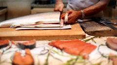 Fishmonger slicing a raw salmon in a fish market in Cagliari, Sardinia. Stock Footage