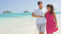 Man showing woman picture on phone app on beach laughing having fun - stock footage