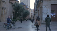 Tourists and bikers walking by the Valencia Cathedral in Valencia Stock Footage