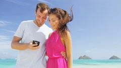 Beach couple on vacation taking smart phone selfie having fun in love Stock Footage