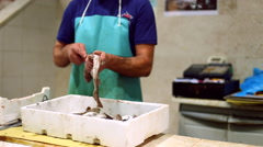 Fishmonger cleaning a dogfish in a fish market, Cagliari, Sardinia. Stock Footage