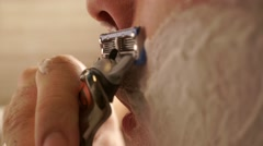 Young handsome man shaving his face, close up profile shot Stock Footage
