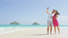 Couple on beach vacation taking selfie smart phone - happy couple in love - stock footage