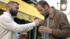 Two, happy male friends standing  with cigarettes and beer in cafe in city, supe Stock Footage