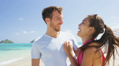 Happy beach couple in love laughing having fun on vacations - Asian woman Stock Footage