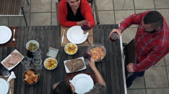 FrieHappy friends raising toast with red wine by table on terrace, top view, sup Stock Footage