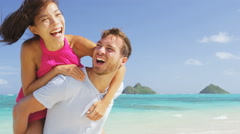 Beach couple having fun laughing on Hawaii holiday travel piggybacking Stock Footage
