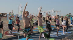 A Group of Young People Making Yoga Exercises in a warm summer day on a beach - stock footage