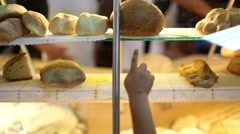 Bread stall in a market with a kid's hand pointing rolls. Stock Footage