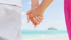 Beach couple in love holding hands on honeymoon travel summer vacation Stock Footage