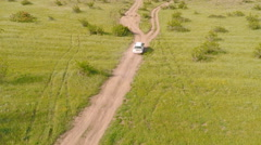 Flying above the car driving offroad through rural countryside Stock Footage