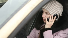 Young girl in winter clothes talking on the phone while sitting behind the wheel Stock Footage