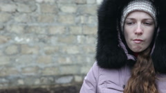 Stock Video Footage of young girl in winter clothes chews the cud, outdoors