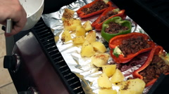 Male hands put potatoes next tap stuffed pepper on the grill, super slow motion Stock Footage