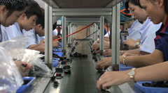 China economy, young factory employees work on conveyor belt Stock Footage