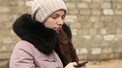 Beautiful woman writing sms in winter clothes on a smartphone Stock Footage