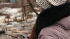 Girl writes sms in winter clothing outdoors rear view Stock Footage