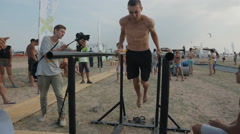 young athlete is pushed on the parallel bars during competition on the street - stock footage