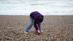 Footage of a woman on a cold winters day beach combing Stock Footage