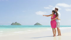 Beach couple holding hands walking on Hawaii - romantic honeymoon vacation - stock footage
