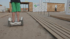 Man in Green Shorts White Hat Riding the Segway on Sand Stock Footage