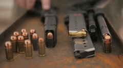 Slow Motion Person Picks Up and Puts Down Handgun Near Stash of Ammunition Stock Footage