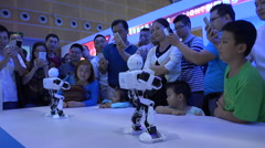Dancing humanoid robots attract a crowd at Shenzhen trade show, China - stock footage