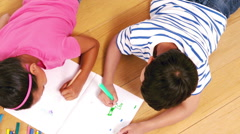 Cute siblings drawing on a notebook in the living room Stock Footage