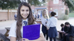 4K Portrait of smiling girl in uniform standing outdoors in school playground Stock Footage