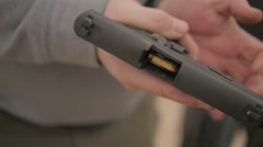 Slow Motion Person Inserts a Magazine Full of Ammo into a Semi Automatic Handgun Stock Footage