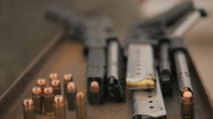 Camera Scans a Table Top Covered with Guns and Ammo 2 Stock Footage