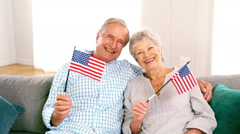Cute mature couple waving american flags in the living room Stock Footage