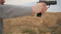 Slow Motion Man Fires Gun Then Admires Shot Stock Footage