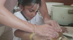 Young adopted indian girl making doughnuts with her dad - stock footage