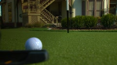 Golfer stroking golf ball into hole, Arkansas, USA Stock Footage