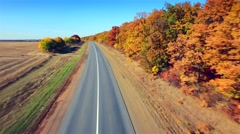 Stock Video Footage of Aerial view of suburban road between field and forest