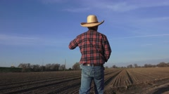Farmer walks onto the land and looks out over the plowed earth readying for a n Stock Footage