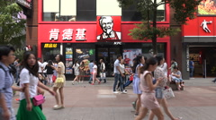 Chinese shppers walk past popular Western fast food restaurant in Wuhan Stock Footage