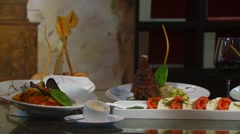 Delicious meal and appetizers set on table Stock Footage