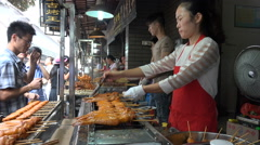Chinese street vendor prepares fresh chicken kebabs at popular food market Stock Footage