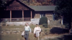 1945: Couple leaving log cabin going golfing carrying golf bags. TRYON, NC Stock Footage