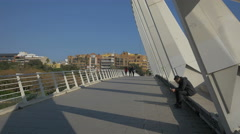 People sitting and walking on Alameda bridge in Valencia Stock Footage