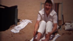 1944: Woman shaking out beach sand from feet seated on canvas chair. TRYON, NC Stock Footage