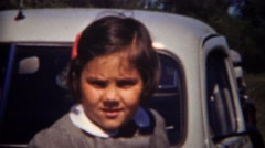 1944: Cute child in grey schoolgirl uniform outdoor gray classic car leaning. Stock Footage