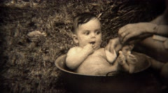 1936: Newborn baby bath washed in a cooking pot outdoor.  TRYON, NC Stock Footage