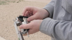 Person Uses Speedloader to Load Bullets into a Revolver Stock Footage