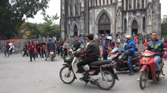 People leave church after Sunday mass by motorbike, in Hanoi, Vietnam Stock Footage