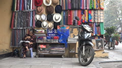 Vietnam tourism, vendor reads newspaper, souvenir stall in old town Hanoi Stock Footage